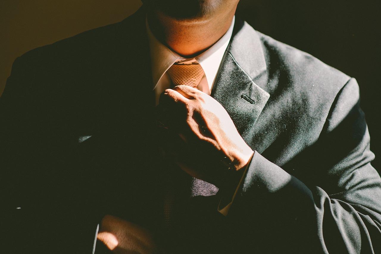 Politician in suit adjusts tie