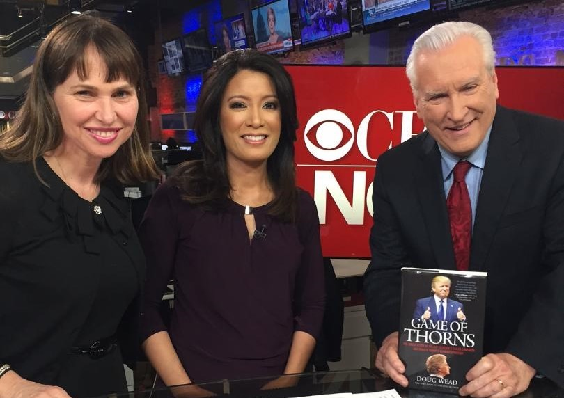Author Doug Wead holds his book Game of Thorns standing next to Elaine Quijano and wife, Myriam on CBS News