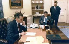 President George H.W. Bush sits at desk in White House across from Chief of Staff, John Sununu sitting in chair and special advisor, Doug Wead standing