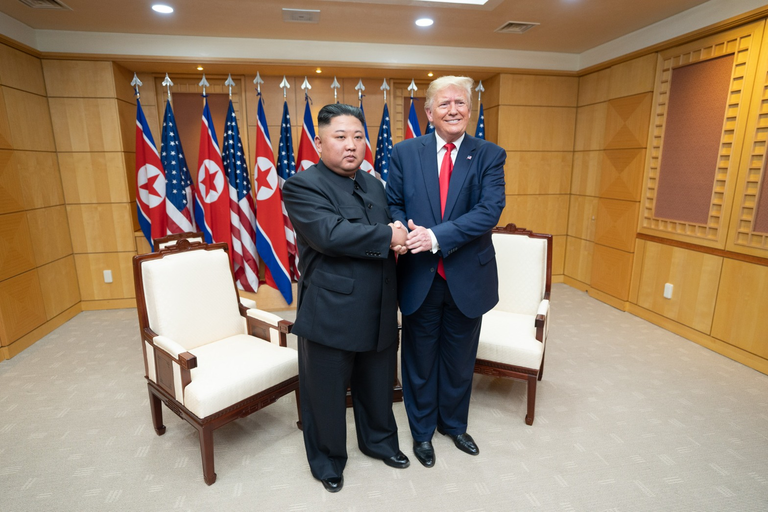 Donald Trump, President of the Unted States, standing with North Korean Leader, Kim Jung-un, shaking hands