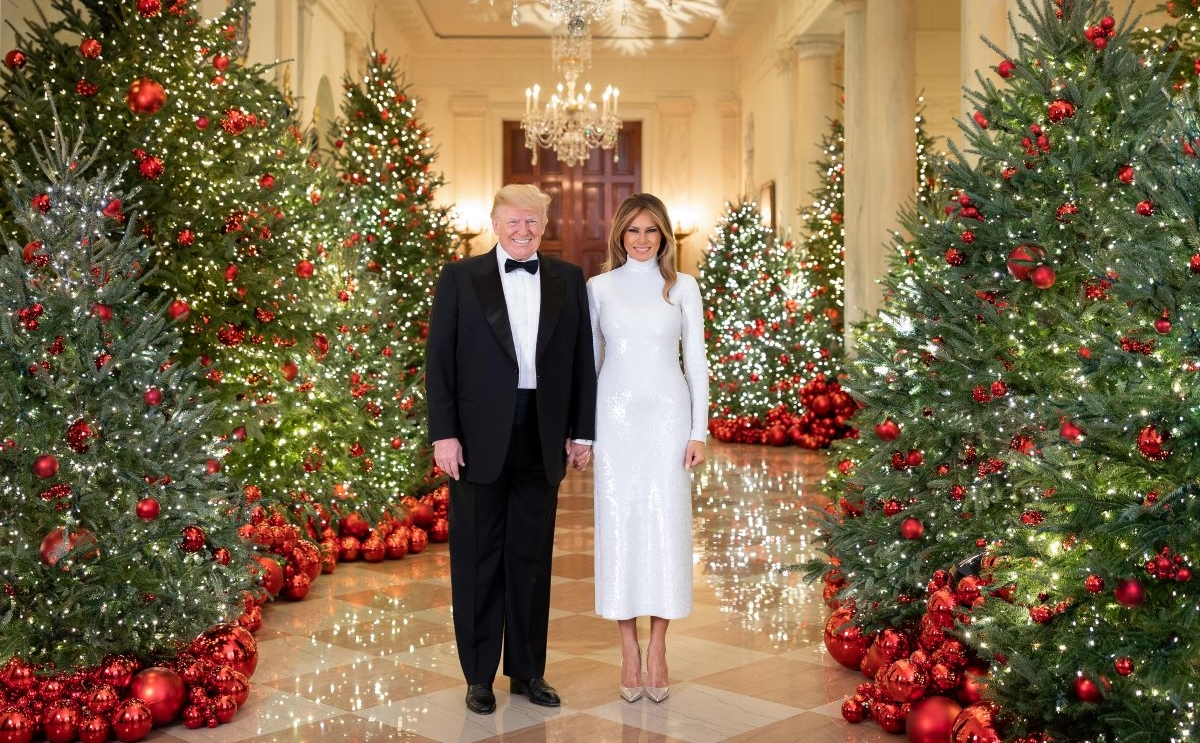 President Trump, and First Lady Melania Trump, stand next to one another, holding hands, surrounded by Christmas trees, in the White House, for Official Christmas portrait