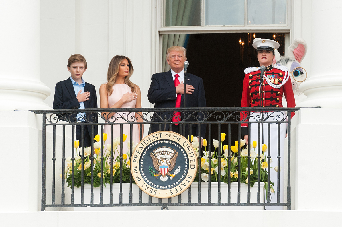President Donald Trump, with First Lady Melania, and son Barron Trump, stand with hands over their hearts, for the national anthem, on Easter